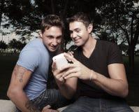 Δύο άτομα που εξετάζουν ένα τηλέφωνο στοκ φωτογραφίες