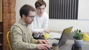 Δύο άτομα που εργάζονται στη συνεδρίαση υπολογιστών στο εμπορικό κέντρο στο εσωτερικό φιλμ μικρού μήκους
