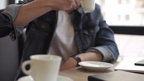 Δύο άτομα που κάθονται στον καφέ κατανάλωσης καφέδων απόθεμα βίντεο