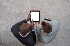 Δύο άτομα που κρατούν την ταμπλέτα και συζητούν την επιχείρηση υπαίθρια Στοκ Εικόνες