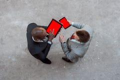 Δύο άτομα που κρατούν την ταμπλέτα και συζητούν την επιχείρηση υπαίθρια Στοκ εικόνα με δικαίωμα ελεύθερης χρήσης