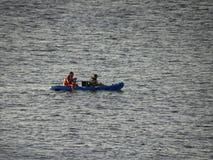 Δύο άτομα που κωπηλατούν σε ένα καγιάκ Στοκ Εικόνες