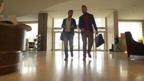 Δύο άτομα που περπατούν στο ξενοδοχείο λόμπι στη χαμηλή γωνία περιστρεφόμενων πορτών υποβάθρου βλέπουν φιλμ μικρού μήκους