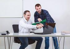 Δύο άτομα που συζητούν και που δείχνουν στο βιβλίο υπολογιστών και σημειώσεων Στοκ φωτογραφία με δικαίωμα ελεύθερης χρήσης