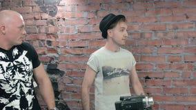 Δύο άτομα πυροβολούν κάποιο στη κάμερα συζήτηση συζήτηση τοίχος εικόνας τούβλου ανασκόπησης rastre απόθεμα βίντεο