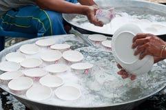 Δύο άτομα πλένουν τα άσπρα πιάτα με το νερό Στοκ Εικόνα