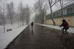 Δύο άτομα στα ποδήλατα που τρέχουν έξω των φαινομένων ενός καιρού - sno Στοκ φωτογραφία με δικαίωμα ελεύθερης χρήσης