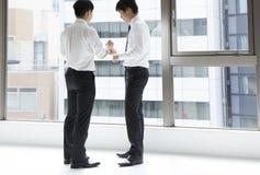 Δύο άτομα στην ομιλία στάσεων μαζί στην αρχή Στοκ φωτογραφίες με δικαίωμα ελεύθερης χρήσης