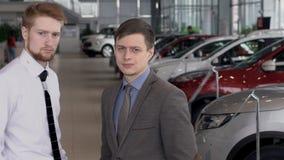 Δύο άτομα στο κλίμα του σαλονιού αυτοκινήτων με τα νέα μοντέλα της μεταφοράς κίνηση αργή απόθεμα βίντεο