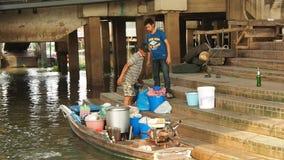 Δύο άτομα φορτώνουν μια επίπεδος-κατώτατη βάρκα απόθεμα βίντεο