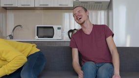 Δύο άτομα χαμογελούν Οι νέοι αστείοι τύποι κάθονται στον καναπέ και το γέλιο πολύ σκληρούς στο αστείο φιλμ μικρού μήκους