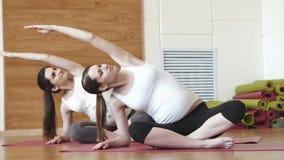 Δύο έγκυοι γυναίκες που κάνουν την άσκηση χαλάρωσης στην άσκηση του χαλιού απόθεμα βίντεο