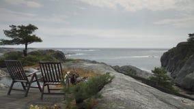 Δύο έδρες με μια τραχιά ωκεάνια άποψη - όχι η τροπική παραλία σας απόθεμα βίντεο