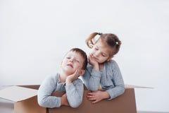 Δύο ένα μικρό παιχνίδι αγοριών και κοριτσιών παιδιών στα κουτιά από χαρτόνι το καλώδιο επιλέγει την έννοια πολλή φωτογραφία κατάλ στοκ φωτογραφία