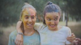 Δύο έφηβη που λερώνονται με τη χρωματισμένη σκόνη Holi ψεκάζουν το νερό στο θερινό πάρκο σε σε αργή κίνηση απόθεμα βίντεο