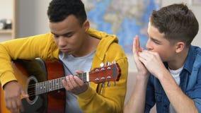 Δύο έφηβοι που παίζουν την κιθάρα και τη φυσαρμόνικα, μουσικό χόμπι, ερασιτεχνικοί μουσικοί απόθεμα βίντεο
