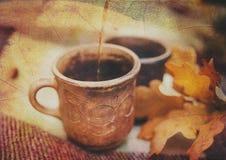Δύο αγροτικά φλυτζάνια αργίλου με το καυτό ποτό είναι στο καρό μαλλιού με τα φθινοπωρινά φύλλα ενάντια ανασκόπησης μπλε σύννεφων  διανυσματική απεικόνιση