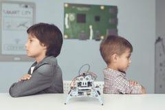 Δύο αγόρια θέτουν σε έναν γκρίζο πίνακα Μεταξύ τους είναι ένα γκρίζο ρομπότ Στοκ Εικόνες