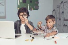 Δύο αγόρια κάθονται στον πίνακα Ένας από τους κάθεται μπροστά από ένα γκρίζο lap-top Λειτουργούν στον πίνακα Στοκ φωτογραφία με δικαίωμα ελεύθερης χρήσης