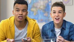 Δύο αγόρια κολλεγίων που προσέχουν την αγαπημένη ομάδα τους στη TV, αθλητικός ανταγωνισμός φιλμ μικρού μήκους