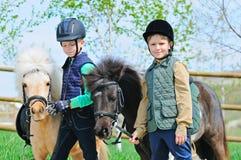 Δύο αγόρια με τα πόνι Στοκ Φωτογραφίες