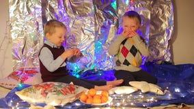 Δύο αγόρια ξεφλουδίζουν και τρώνε tangerines φιλμ μικρού μήκους