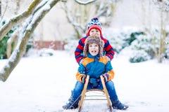 Δύο αγόρια παιδάκι που απολαμβάνουν το γύρο ελκήθρων το χειμώνα Στοκ εικόνες με δικαίωμα ελεύθερης χρήσης