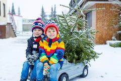 Δύο αγόρια παιδάκι που οδηγούν το αυτοκίνητο παιχνιδιών με το χριστουγεννιάτικο δέντρο Στοκ Εικόνα