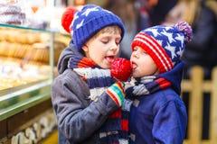 Δύο αγόρια παιδάκι που τρώνε τη στάση γλυκών μήλων ζάχαρης στην αγορά Χριστουγέννων Στοκ Φωτογραφία