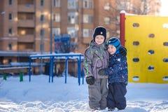 Δύο αγόρια παιδάκι στα ζωηρόχρωμα ενδύματα που παίζουν υπαίθρια κατά τη διάρκεια των χιονοπτώσεων Ενεργός ελεύθερος χρόνος με τα  Στοκ εικόνα με δικαίωμα ελεύθερης χρήσης