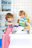 Δύο αγόρια παιδάκι που πλένουν τα πιάτα στην εσωτερική κουζίνα Στοκ εικόνες με δικαίωμα ελεύθερης χρήσης