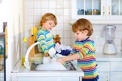 Δύο αγόρια παιδάκι που πλένουν τα πιάτα στην εσωτερική κουζίνα Στοκ Εικόνες