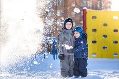 Δύο αγόρια παιδάκι στα ζωηρόχρωμα ενδύματα που παίζουν υπαίθρια κατά τη διάρκεια των χιονοπτώσεων Ενεργός ελεύθερος χρόνος με τα  Στοκ Εικόνες