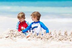 Δύο αγόρια παιδιών που στηρίζονται το κάστρο άμμου στην τροπική παραλία του Playa del Carmen, Μεξικό Στοκ Εικόνες