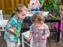 Δύο αγόρια που εξετάζουν κάθε άλλα χρωματισμένα αυγά Πάσχας Στοκ φωτογραφίες με δικαίωμα ελεύθερης χρήσης