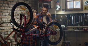 Δύο αγόρια που επισκευάζουν ένα ποδήλατο σε ένα γκαράζ φιλμ μικρού μήκους