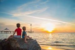 Δύο αγόρια που κάθονται στο βράχο στην παραλία στο ηλιοβασίλεμα στοκ εικόνα με δικαίωμα ελεύθερης χρήσης