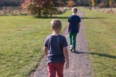 Δύο αγόρια που περπατούν προς τα εμπρός σε μια πορεία με την πλάτη που αντιμετωπίζει τη κάμερα στοκ εικόνα