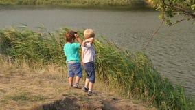 Δύο αγόρια ρίχνουν τις πέτρες στη λίμνη στη θερινή ημέρα απόθεμα βίντεο