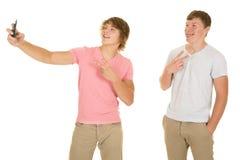 Δύο αγόρια στέκονται εξετάζουν το τηλέφωνο παίρνουν την εικόνα Στοκ Φωτογραφία