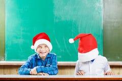 Δύο αγόρια στα καπέλα santa έχουν τη διασκέδαση ενάντια στον πίνακα Στοκ Εικόνα