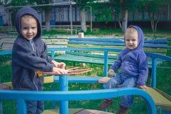 Δύο αγόρια στο γύρο μπλε ζακετών Στοκ Εικόνες