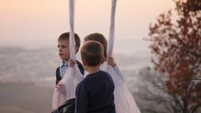 Δύο αγόρια τινάζουν τη μικρή αδελφή τους σε μια ταλάντευση κάτω από ένα μεγάλο δέντρο φιλμ μικρού μήκους