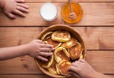 Δύο αγόρια τρώνε τις σπιτικές τηγανίτες με το μέλι Στοκ Εικόνα