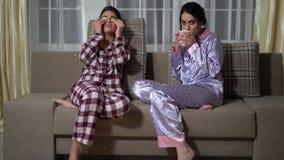 Δύο αδελφές διδύμων χαλαρώνουν το βράδυ σε ένα άνετο καθιστικό, προσέχοντας έναν κινηματογράφο, κάνοντας ένα μάτι αγγουριών να κα απόθεμα βίντεο