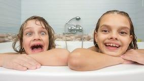 Δύο αδελφές λούζουν στο λουτρό και κάνουν τα πρόσωπα διασκέδασης στοκ φωτογραφία με δικαίωμα ελεύθερης χρήσης