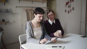Δύο αδελφές που χρησιμοποιούν τη συνεδρίαση PC ταμπλετών στον πίνακα στο σπίτι Η γυναίκα έχει τη διασκέδαση με την ταμπλέτα απόθεμα βίντεο