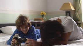 Δύο αδελφοί που βρίσκονται στο κρεβάτι παίζουν με τα παιχνίδια Παλαιότερος και μικρότεροι αδερφοί που έχει τη διασκέδαση από κοιν φιλμ μικρού μήκους
