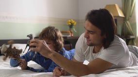 Δύο αδελφοί που βρίσκονται στο κρεβάτι παίζουν με την τίγρη και το άλογο παιχνιδιών Παλαιότερος και μικρότεροι αδερφοί που έχει τ απόθεμα βίντεο