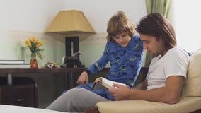 Δύο αδελφοί που κάθονται στην καρέκλα βραχιόνων, παλαιότερος αδελφός διαβάζουν για το μικρό αδελφό ένα βιβλίο και αυτοί που γελού φιλμ μικρού μήκους